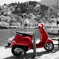 Bright red scooter with the port of Symi in Greece in black and white in the background Royalty Free Stock Photo