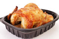 Rotisserie chicken to go dinner cooked and packaged by grocery store and brought home ready serve still in plastic contain against Stock Image