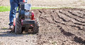 Rototiller cultivator in the garden Royalty Free Stock Photo