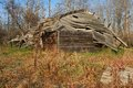 Rotting old barn with rusty mower in foreground nearly fully collapsed a grassy field a the Royalty Free Stock Images
