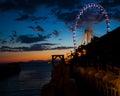 Roue de Ferris sur l'eau au coucher du soleil Photographie stock libre de droits