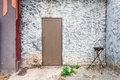 Rough concrete wall with wood door and fire torch stand Royalty Free Stock Photography