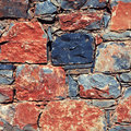 Rough mediterranean stone wall as background red and gray square toned image instagram effect Stock Photos