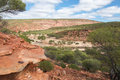 Rough terrain at kalbarri national park with the sandy dried out murchison river gorge in with green plants and layered red Royalty Free Stock Photo