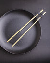 Round black plate with chopsticks for sushi Royalty Free Stock Photo