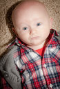 Round face baby boy with big blue eyes cute wide open looking to the side wearing a plaid shirt and vest Royalty Free Stock Images
