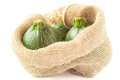Round green zucchini in ackcloth bag on white Stock Photos