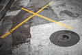 Round hatch on asphalt road with yellow marking lines Stock Image
