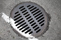Round hatch and white dividing line on urban asphalt road Royalty Free Stock Photos