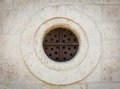 Round metal window in a stone wall Stock Photo