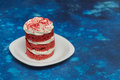 Round red velvet cake with cream on white plate Royalty Free Stock Photo