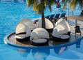 Round relaxing beds by swimming pool circular and loungers with shades side of hotel Stock Photos