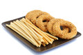 Round rusks and bread sticks on plate isolated on white background Royalty Free Stock Images