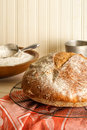 Round rustic artisan bread a cools on a wire baking rack resting on a sunlit table surrounded by baking utensils and a bowl of Stock Photo