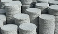 Round stone slabs lots of stacked grey granite in sunny ambiance Royalty Free Stock Images