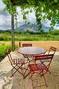 Round table in vine-covered outdoor cafe in mountains Royalty Free Stock Photo