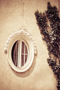 Round window wooden on old building with liana on wall Royalty Free Stock Photography