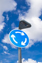 Roundabout sign the street with brilliant blue and cloudy skies Royalty Free Stock Photography