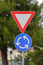 Roundabout sign triangle and traffic signs at circular intersection approach Stock Images