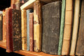 Row of antique books old cover spines on the shelf Stock Photo