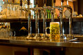 Row of beer taps in a pub with a tankard of beer stainless steel on wooden counter for dispensing draught large glass Stock Photography