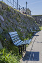 A row of benches in front of varbergs fästning the stone walls the fortress varberg historic fortress that has been Stock Photo