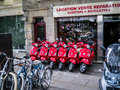 Row of bright red motor scooters parked outside dealership on sidewalk in paris six a tight line a sales and repair shop Royalty Free Stock Photography
