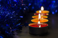 A row from burning candles and a Christmas decor Royalty Free Stock Photo