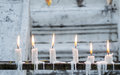 Row of burning candles with white temple wall as background Royalty Free Stock Photo