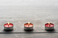 Row of burning red tealights or small candles on a dark wooden surface with copyspace above Royalty Free Stock Photo