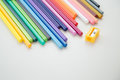 Row of color pencil crayons colorful and sharpener on white desktop Royalty Free Stock Image