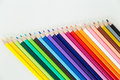 Row of color pencil crayons colorful on white desktop Royalty Free Stock Images