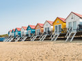 Row of colorful beach huts in the sand sandy with cabanas with white stairs a Stock Images