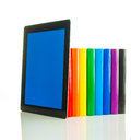 Row of colorful books and tablet pc over white background Stock Photo
