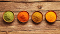 Row of colorful spices in bowls viewed from above on a wooden table with ginger cayenne chili powder turmeric and matcha or Royalty Free Stock Photo