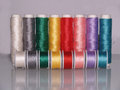 Row of colourful sewing threads with bobbins matching white grey green yellow red pink violet and turquoise all placed in a on a Royalty Free Stock Photo