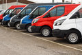 Row of different marques of commercial vehicles or vans for retail sale on a motor dealers lot all logos removed Stock Image