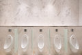 Row of five urinals with infrared sensor, on marble wall, in men's public toilet Royalty Free Stock Photo