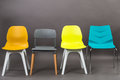 Row of four color plastic chairs isolated on gray background. Furniture series. Royalty Free Stock Photo