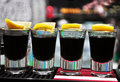 Row of four drinks of black vodka on the bar Stock Images