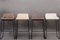 Row of four modern bar chairs isolated on gray background. Furniture series.