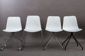 Row of four white plastic chairs isolated on gray background. Furniture series. Royalty Free Stock Photo
