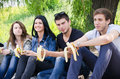 Row of friends sitting together eat banana Royalty Free Stock Photo
