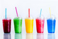 Row of frozen fruit slushies in plastic cups panoramic still life colorful slush granita drinks take away with lids and drinking Stock Photo