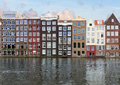 Row of historic buildings amsterdam over canal waters netherlands Royalty Free Stock Image