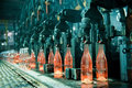 Row of hot orange glass bottles in factory Royalty Free Stock Photos