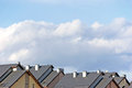 Row house roofs, condo rooftop panorama and bright summer clouds sunny cloudscape Royalty Free Stock Photo