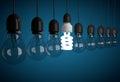 Row of incandescent bulbs lit by one energy saving bulb