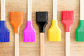 Row of kitchen brushes with colorful bristles line in the colours the rainbow for decorating and glazing pastries or basting meat Royalty Free Stock Image