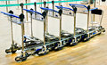 Row of luggage carts a in airport Stock Photos